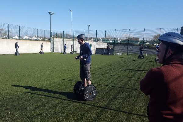 Segways driving around on astroturf surface.