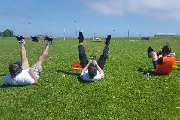 Players lying on the grass with catapult attached to feet.