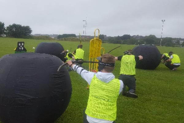 Group of players enjoying Battle Zone Archery on grass surface.